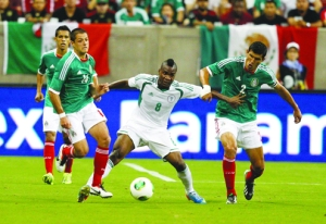 •GRITTY: Nigeria's Brown Ideye (middle) fends off Javier Hernandez (left) and Francisco Rodiriguez (right) of Mexico as he attempts to gain control of the ball during the friendly match at Reliant Stadium on 31 May, 2013 in Houston, Texas. The game ended 2-2 draw. PHOTO: AFP.