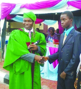 •Director, Good Shepherd Schools, Dr. Bayo Oyeyemi shaking hands with the overall best student of the school, Master Sanni Fawaaz