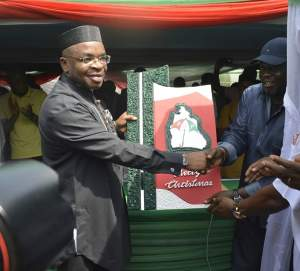 L-R :Akwa Ibom State Governor, Mr Udom Emmanuel (left) receiving a Christmas Card from the State Chairman of the Peoples Democratic Party (PDP), Obong Paul Ekpo, during his visit to the Party Secretariat in Uyo.