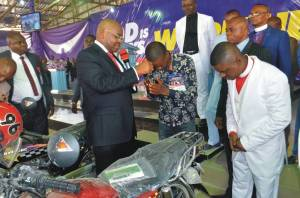 Governor Udom Emmanuel presenting a motorcycle key to Mr. Friday Jackson on behalf of the General Overseer of The Apostolic Mount Oliver Church, Prophet (Dr.) David Udo Udo.