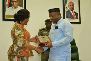 Gov Udom Emmanuel of Akwa Ibom State presenting a plague to the Director-General of National Council for Arts and Culture, Mrs Dayo Keshi