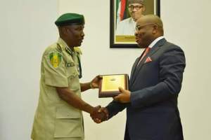 Gov Udom Emmanuel presenting a plague to the Comptroller-General of the Nigerian Prisons Service, Mr Ahmed Ja'afaru